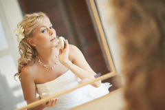 Gorgerous bride standing in front of mirror and fixing her hair Stock Image