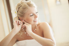 Gorgerous bride standing in front of mirror and fixing her hair Stock Photography