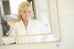 Gorgerous bride standing in front of mirror and fixing her hair Stock Images