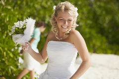 Gorgerous bride walking to wedding ceremony on the beach with bo Stock Photos
