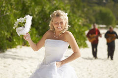 Gorgerous bride walking to wedding ceremony on the beach with bo Royalty Free Stock Photo