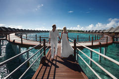 Gorgerous just married couple walking to villa by bridge after w. Edding. Beautiful sunny day in paradise. Caribbean, Hawaii or Cancun wedding Royalty Free Stock Photos