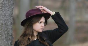 Gorgeus brązowowłosa dziewczyna w retro projektującym odziewa zostawać na miastowej ulicie, załatwiający jej włosy, czeka someone zdjęcie wideo