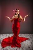 Gorgeus-Mädchen in einem roten Kleid mit Blume im Haar Lizenzfreie Stockfotografie