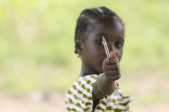 Gorgoeus African girl holding pen in front of her face. Young girl holding pen in hand and looking at camera on blurred background Royalty Free Stock Image