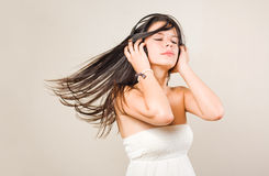 Gorgoeus young brunette immersed in music. Royalty Free Stock Photography