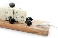 Gorgonzola with black olives closeup. Blue cheese and black olives on cheeseboard on white background Royalty Free Stock Photo