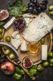 Gorgonzola and Camembert cheese with Knife for cheese  white and dark grapes, honey and jam on  wooden cutting board on a dark ru Royalty Free Stock Photo