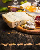Gorgonzola Camembert on a wooden cutting board with a knife for cheese with honey and jam light grape on dark wooden background cl Stock Photos