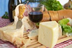 Gorgonzola, parmezaan, pecorinokaas, met wijn en brood Stock Afbeeldingen