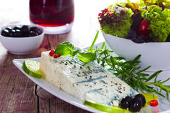 Gorgonzola with salat and olives. Stillife of gorgonzola with salat, red wine,olives, basil and rosemary Royalty Free Stock Photos