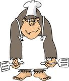 Gorila con un delantal y 2 espátulas Imágenes de archivo libres de regalías