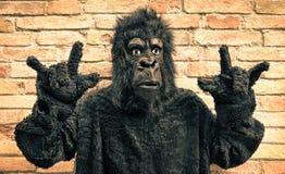 Gorila falso divertido con gesto de mano del rock-and-roll Foto de archivo