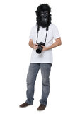Gorilla man with a DSLR camera. Man with a gorilla mask, isolated on a white background, holding a DSLR camera Stock Images