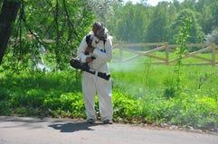 GORKI LENINSKIE, ΡΩΣΊΑ - 11 ΜΑΐΟΥ 2016: GORKI LENINSKIE, ΡΩΣΊΑ - 11 ΜΑΐΟΥ 2016: Το άτομο στις φόρμες διευθύνει τη acaricidal επεξ Στοκ φωτογραφία με δικαίωμα ελεύθερης χρήσης
