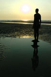 Gormley statue on the beach at Liverpool. One of the many identical Gormley bronze statues placed on the beach near Liverpool in the UK royalty free stock photo