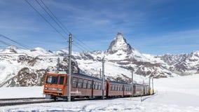 Gornergrat Train in front of Matterhorn. Zermatt, Switzerland - April 12, 2017: The red Gornergrat Train in front of the snowy Matterhorn mountain stock image