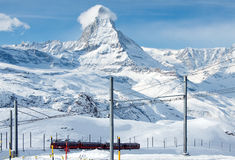The Gornergratbahn with Matterhorn in background. ZERMATT – JANUARY 17: Red train climbing up to Gornergrat station with Matterhorn in the background on stock photo