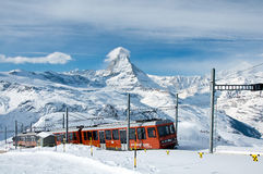 The Gornergratbahn. ZERMATT – JANUARY 17: Red train climbing up to Gornergrat station with Matterhorn in the background on January 17, 2013 in Zermatt stock photography