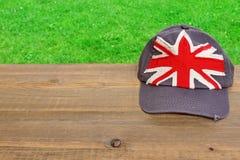 Gorra de béisbol con la bandera británica en la tabla de madera Imagen de archivo