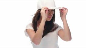 Gorra de béisbol que lleva y camisa de la mujer joven de la belleza almacen de metraje de vídeo