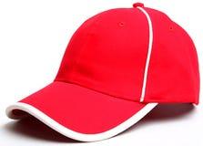 Gorra de béisbol roja en un casquillo blanco del fondo Imagenes de archivo