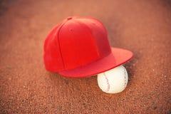 Gorra de béisbol y bola en campo imagenes de archivo