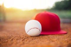 Gorra de béisbol y bola en campo foto de archivo
