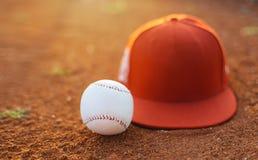 Gorra de béisbol y bola en campo imágenes de archivo libres de regalías