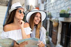 Gorup de sorriso dos amigos com mapa Turismo, curso, lazer, feriados e conceito da amizade imagem de stock