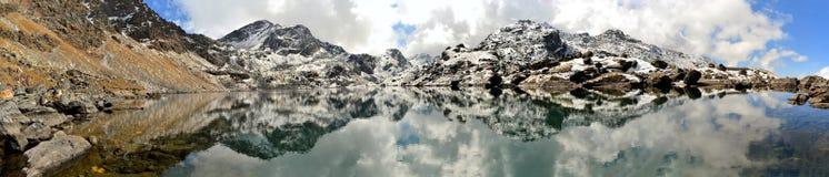 Gosainkunda Mirror Lake, Himalayas, Nepal. Reflection of mountain and snow at sacred Hindu Gosainkunda Mirror lake in the Langtang Himalaya mountain range, Nepal Stock Image