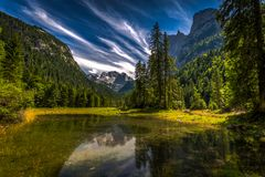 Gosaulacke, small and blue pond under Dachstein in Austria with green trees and glacier in the background royalty free stock images