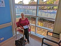 Gosford Hospital building progress H56ed October 2018. Gosford, New South Wales, Australia - October 23, 2018: Senior lady patient seated in the Cardiac waiting royalty free stock photo