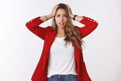 Gosh have trouble. Portrait of panicking worried young cute silly female trainee wearning red jacket holding hands head royalty free stock photos
