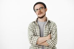 Gosh stop talking you getting me sick. Irritated bothered and annoyed young caucasian guy with beard in transparent. Glasses and beanie rolling eyes up and stock photo