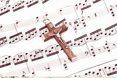 Gospel. Crucifix on top of Sheet Music Royalty Free Stock Image