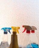 Gospodarstwa domowego cleaning produkty w kiści butelkach obok okno - r zdjęcie stock