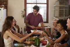 Gospodarz i przyjaciele przechodzimy karmowego round przy obiadowym przyjęciem stół fotografia stock