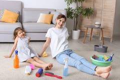 Gospodyni domowa i córka odpoczywa po czyścić obrazy royalty free