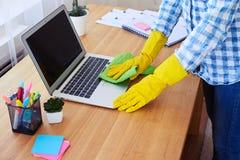 Gospodyni domowa odkurza laptop w rękawiczkach Zdjęcie Stock