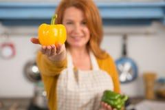 Gospodyni domowa trzyma jaskrawego koloru żółtego pieprzu w ręce Fotografia Royalty Free