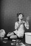 Gospodyni domowa w włosianych curlers i gumowych rękawiczkach maluje wargi pomadkę zdjęcie stock