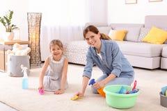 Gospodyni domowa z córki cleaning dywanem fotografia royalty free