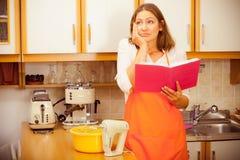 Gospodyni domowa z książką kucharska w kuchni Zdjęcia Royalty Free