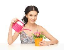Gospodyni domowa z kwiatem w garnku i podlewanie puszce zdjęcie stock