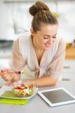 Gospodyni domowej łasowania owoc sałatka i używać pastylka komputer osobistego Obraz Stock