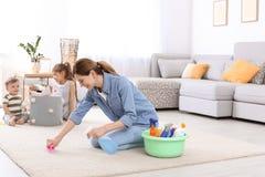 Gospodyni domowej cleaning dywan podczas gdy jej dzieci zdjęcia stock