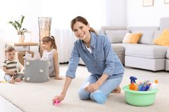 Gospodyni domowej cleaning dywan podczas gdy jej dzieci fotografia royalty free