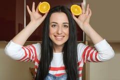 Gospodyni domowej mienia pomarańczowi plasterki nad ona kierownicza i ma zabawę fotografia stock