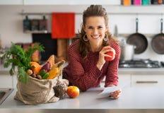 Gospodyni domowej mienia sklepu spożywczego zakupy czeki fotografia stock